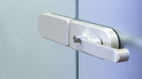 Modern metal office door handle on a glass door